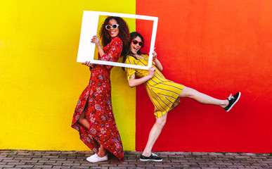 Wall Mural - Girls posing with empty picture frame