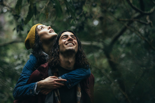 Lovely couple piggybacking in the park under rain