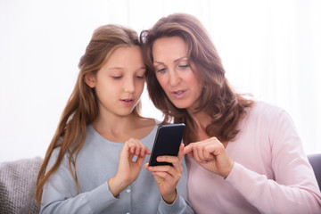 Mother And Daughter Using Cellphone