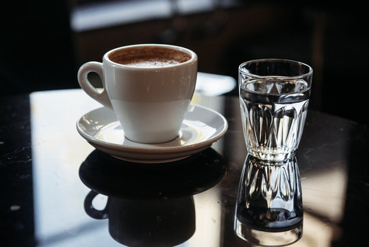 Close-up of a cup of coffee and glass of water on a table