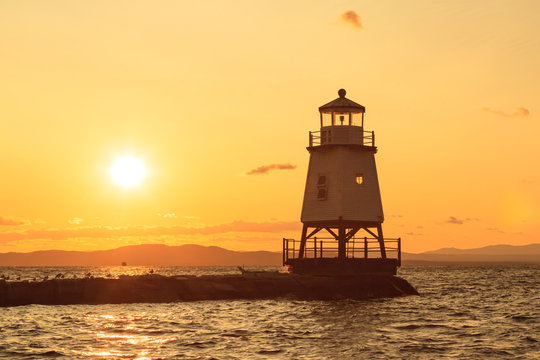 A beautiful orange sunset behind a lighthouse in front of Burlington Vermont