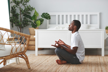 young black man doing yoga and sitting in lotus position at home in bedroom