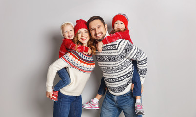 happy family mother, father and children in knitted hats and sweaters on gray background