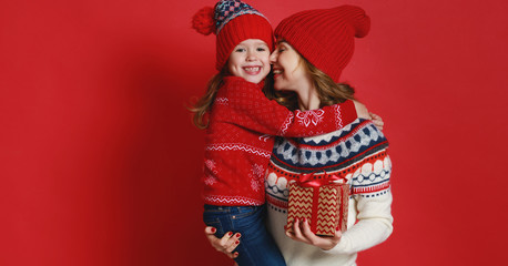happy family mother and child daughter with christmas gifts on red background