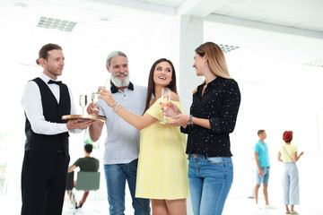 Waiter serving champagne to group of people at exhibition in art gallery