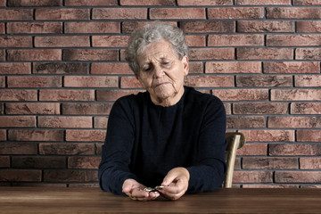 Poor elderly woman counting coins at table