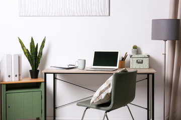 Stylish and comfortable workplace with modern laptop in office