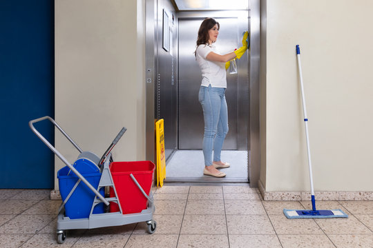 Female Janitor Wearing Gloves Cleaning Elevator