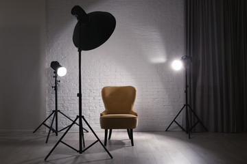 Interior of modern photo studio with professional lighting equipment and armchair