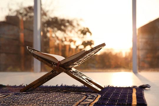 Rehal with open Quran on Muslim prayer rug indoors