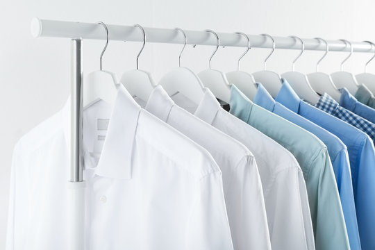 Men's clothes hanging on wardrobe rack against white background
