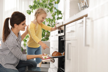 Mother and daughter taking out buns from oven in kitchen