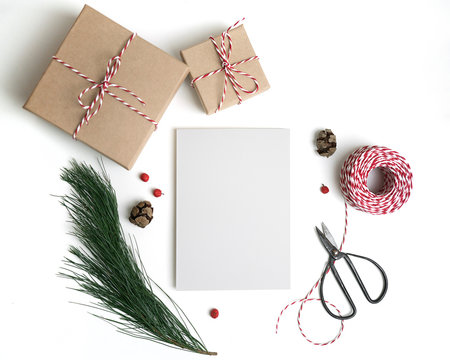 Christmas card mockup. New year craft flat lay, top view, copy space. Paper blank mock up, gift boxes, scissors, decorations, pine cones, isolated on white background.