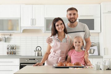 Happy family with tray of freshly oven baked buns at table in kitchen. Space for text