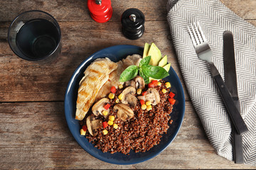 Plate with quinoa and garnish on table, top view
