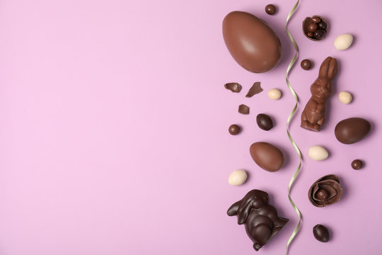 Flat lay composition with chocolate Easter eggs and space for text on color background