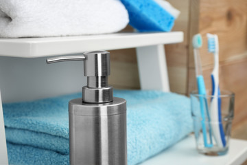 Metal soap dispenser on shelf in bathroom. Space for text