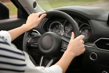 Woman holding steering wheel in car, closeup. Driving license test