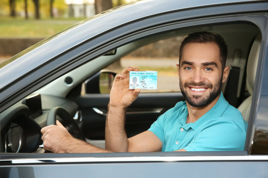 Young man holding driving license in car