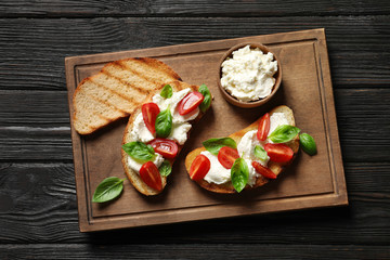 Toasted bread with tasty cream cheese and tomatoes on wooden table, flat lay