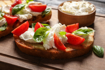 Toasted bread with tasty cream cheese and tomatoes on wooden board