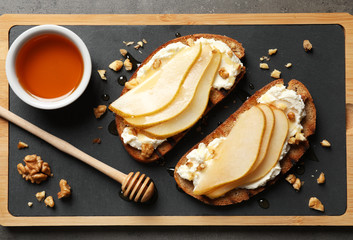 Toasted bread with tasty cream cheese and pear on board, flat lay