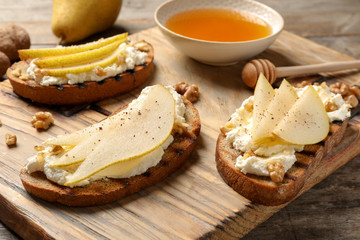 Toasted bread with tasty cream cheese and pear on wooden board