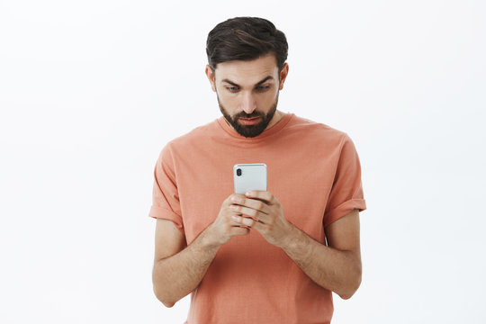 Man attention captured with smartphone. Interested bearded guy carried away with awesome app or game looking at mobile phone screen excited and curious typing message, standing over gray wall