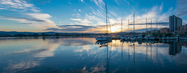 Boats moored on the port of Olbia at sunset, Sardinia, Italy Wall mural