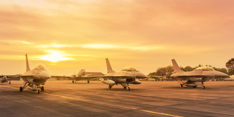 Falcon fighter jet military aircraft parked on runway in the base airforce standby ready to take off for military mission on sunset