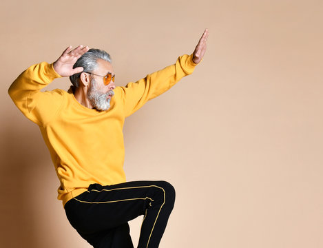 Happy senior millionaire man dancing in yellow sunglasses stylish fashionable men senior