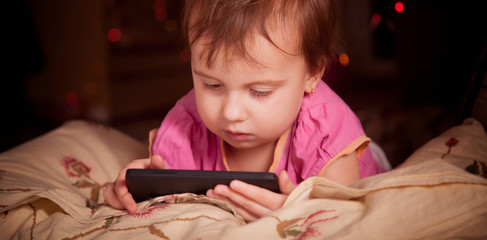 Little child girl using the smart phone on the bed before she sleeping at night. Mobile addict concept.