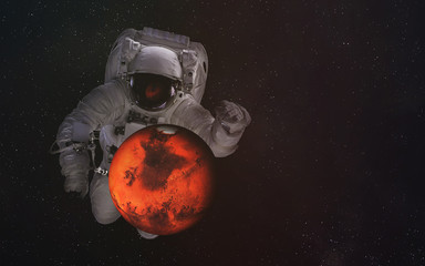 Single giant astronaut in outer space with Mars. Elements of this image were furnished by NASA.