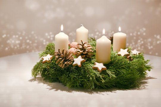 Third Advent - decorated Advent wreath from fir and evergreen branches with white burning candles, tradition in the time before Christmas, warm background with festive bokeh and copy space