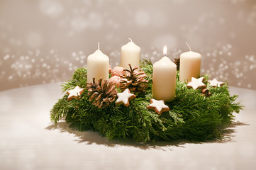 Fototapeta First Advent - decorated Advent wreath from fir and evergreen branches with white burning candles, tradition in the time before Christmas, warm background with festive bokeh and copy space obraz