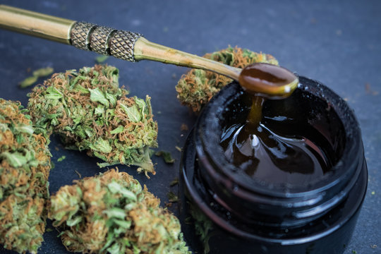 """Cannabis flower with concentrated THC/CBD extract """"sauce"""" wax on dab tool"""