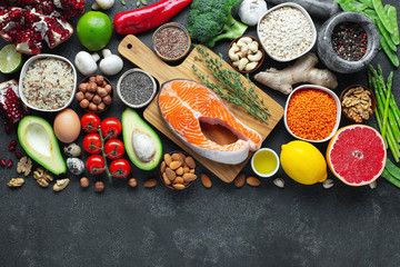 Healthy food clean eating selection: fish, fruit, nuts, vegetable, seeds, superfood, cereals, leaf vegetable on black concrete background with copy space. Flat lay