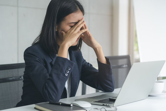 Asian office worker having an eyes tired after overwork