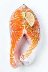 Raw fresh salmon or trout steak, rich in omega-3 oil, with lime, thyme and olive oil on a white background. Healthy and dietary food. Top view. Flat lay