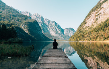 Person sitting on lake side with mountains at a distance