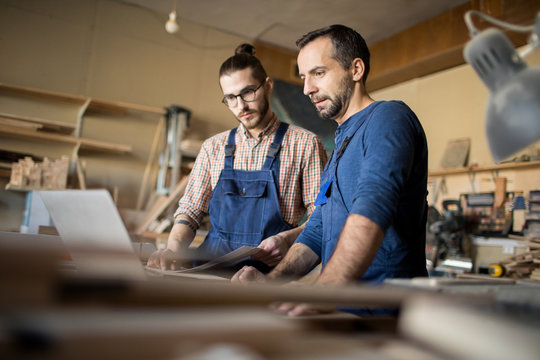 Low angle portrait of two modern artisans using laptop in workshop while working with wood together, copy space