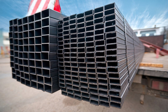 Bent metal profile channel on the truck. Ready for delivery. Steel materials, construction supplies. Coated profiles in the rack. Metal profile pipe of rectangular cross section in packs at warehouse