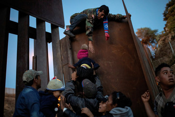 Migrants from Honduras, part of a caravan of thousands from Central America trying to reach the United States, try to jump a border fence to cross illegally from Mexico to the U.S, in Tijuana