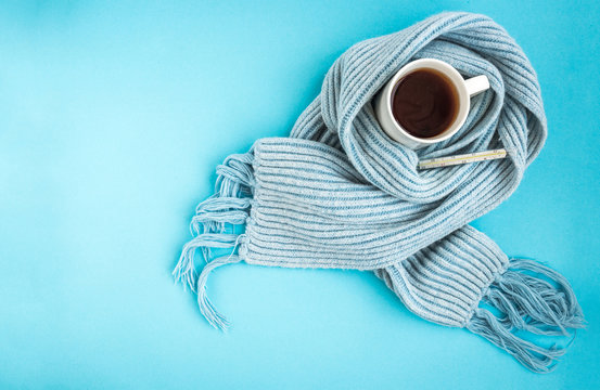 White mug of tea with blue scarf and thermometer on blue background. Disease and health concept.