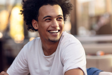 Close up portrait of handsome cheerful african man smiling looking at camera.