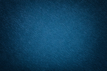 Textural of navy blue background of wavy corrugated paper, closeup.
