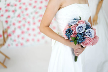 Bride in dress holding wedding bouquet of flowers and greenery,Happy wedding concept.