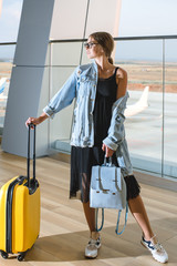 Beautiful young woman at the airport with a yellow suitcase and blue backpack.