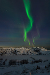 Beautiful northern lights, aurora in the night sky above the snow-covered hills. Large stones and a frozen lake.