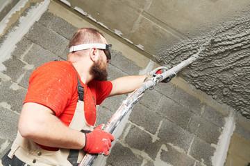 Plasterer using sprayer machine putting plaster mortar on ceiling